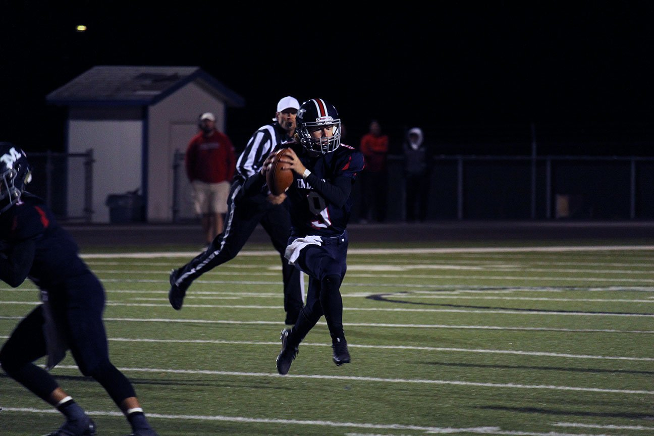 Scouting the feild. Sophomore Quaterback Dayne Aschenbrenner scrambles as he tries to find an open reciever down the feild in the Red Zone. Manhattan High remains undefeated after finishing with a score of 41 to 14 against Emporia on Homecoming Night. Photo by Mason Alberto   Photo by Mason Alberto