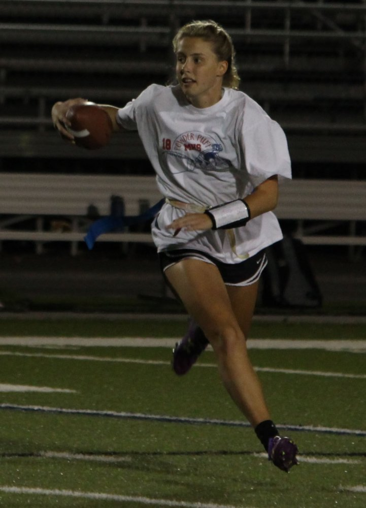 TUCK AND RUN. Senior Ally Brickei runs away from pressure as the pocket collapses. The Tomahawks ran away with a win scoring 12 unanswered points shutting out the opposing team.