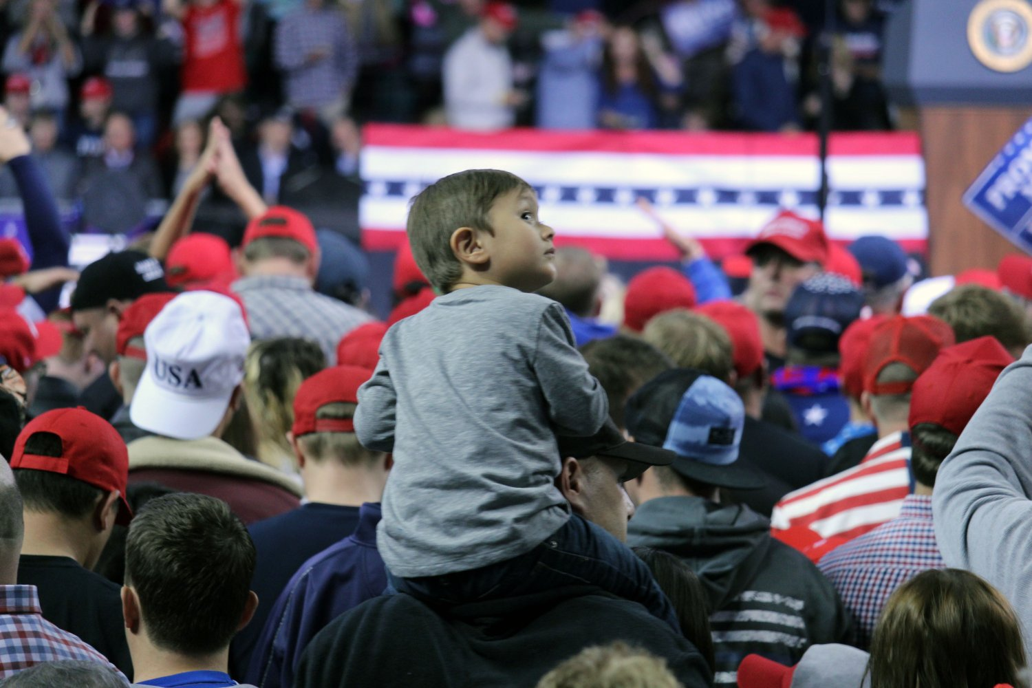 A little boy looks back as he sits on his father's shoulders at a rally for Donald Trump on Oct. 6 in Topeka, Kansas. The rally brought in a crwod of nearly 11 thousand people in support of Trump's 2020 campaign for president.