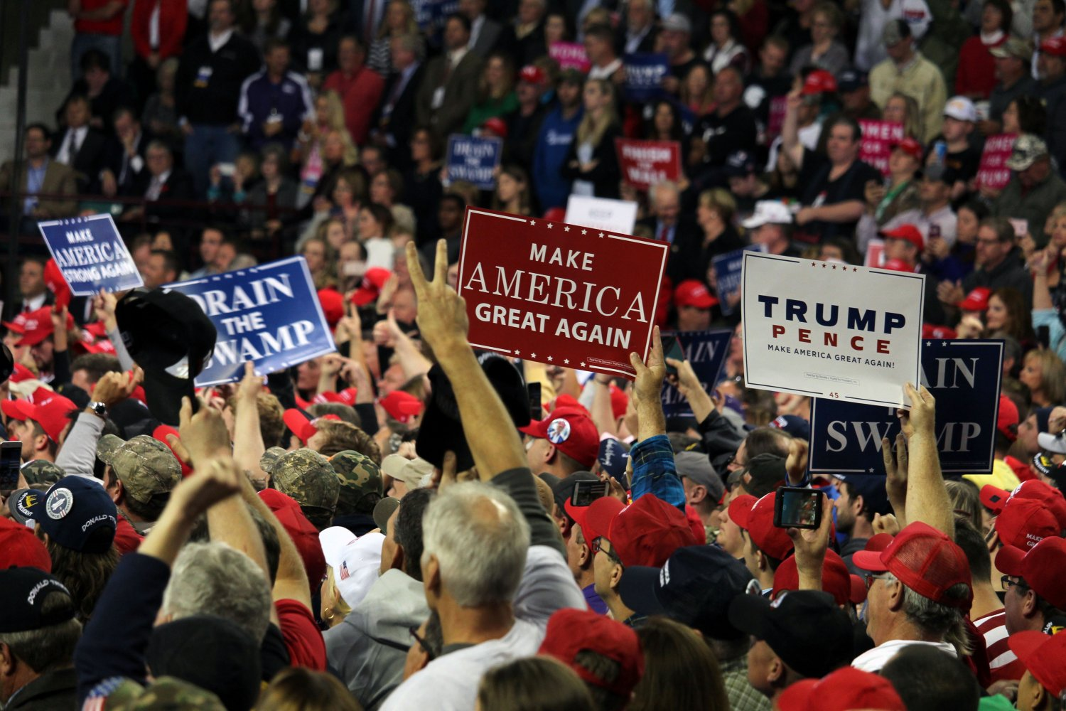 Fans hold up supportive signs with President Donald Trump's slogans. They gathered at the Expo Center in Topeka, Kansas on Oct. 6 to see Trump and fellow politicinas Kris Kobach and Steve Watkins address the crowd.