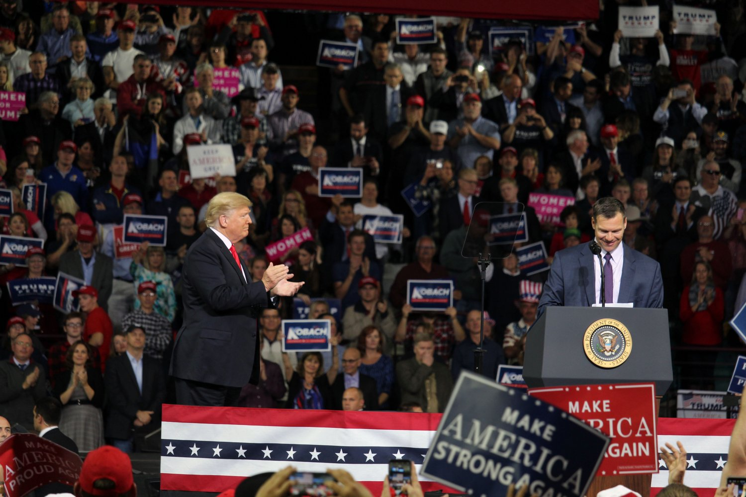 President Donal Trump applauds as he hands off the microphone to Kris Koback. Kobach, who is running for Governor of Kansas, spoke along with Trump at a rally in Topeka, Kansas on Oct. 6 after recieving personal endorsement from him and his campaign.