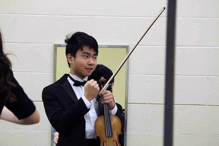 Senior Allen Zhang gives the rest of Chamber Orchestra a pep talk before they go out on stage. He urged them all to feel each emotion as they played, hoping that it would help them all to remember what they were trying to express. Photo by Sophia Comas