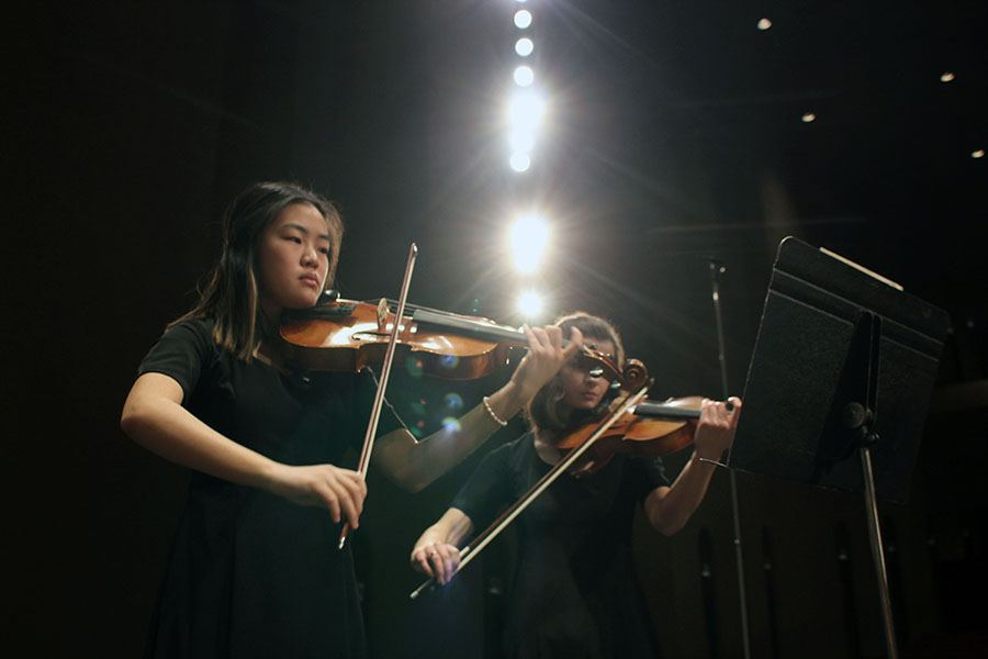 Sophomore Amy Joo and junior Audrey Parish play thier viola parts for String Quartet No. 8 on stage within the Century II theater in Wichita. They and the rest of Chamber performed for the KMEA conference where nine also played for the All-State orchestra. Photo by Sophia Comas