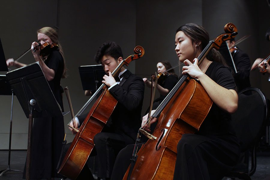 Seniors Joanna Park and Chris Chae play their cello parts onstage for their KMEA performance. The piece was meant to reflect the emotional angst of the composer, who contemplated suicide while writing it. Photo by Sophia Comas