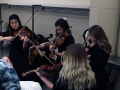 Sophomore Amy Joo, junior Audrey Parish, and seniors Liz Efken and Grace Hart practice their viola parts in thier dressing room as they wait to go onstage for their KMEA performance. The group played String Quartet No. 8 by Dmitri Shostakovich wihout the direction of Nate McClendon, completely relying on each other for guidance. Photo by Sophia Comas