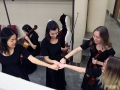 Sophomore Amy Joo, junior Audrey Parish, and seniors Liz Efken and Grace Hart fist bump after successfully practicing a viola part in String Quartet No. 8. They and the res of Chamber used their time in the dressing room to quickly rehearse small parts before they went on stage for thier KMEA performance. Photo by Sophia Comas