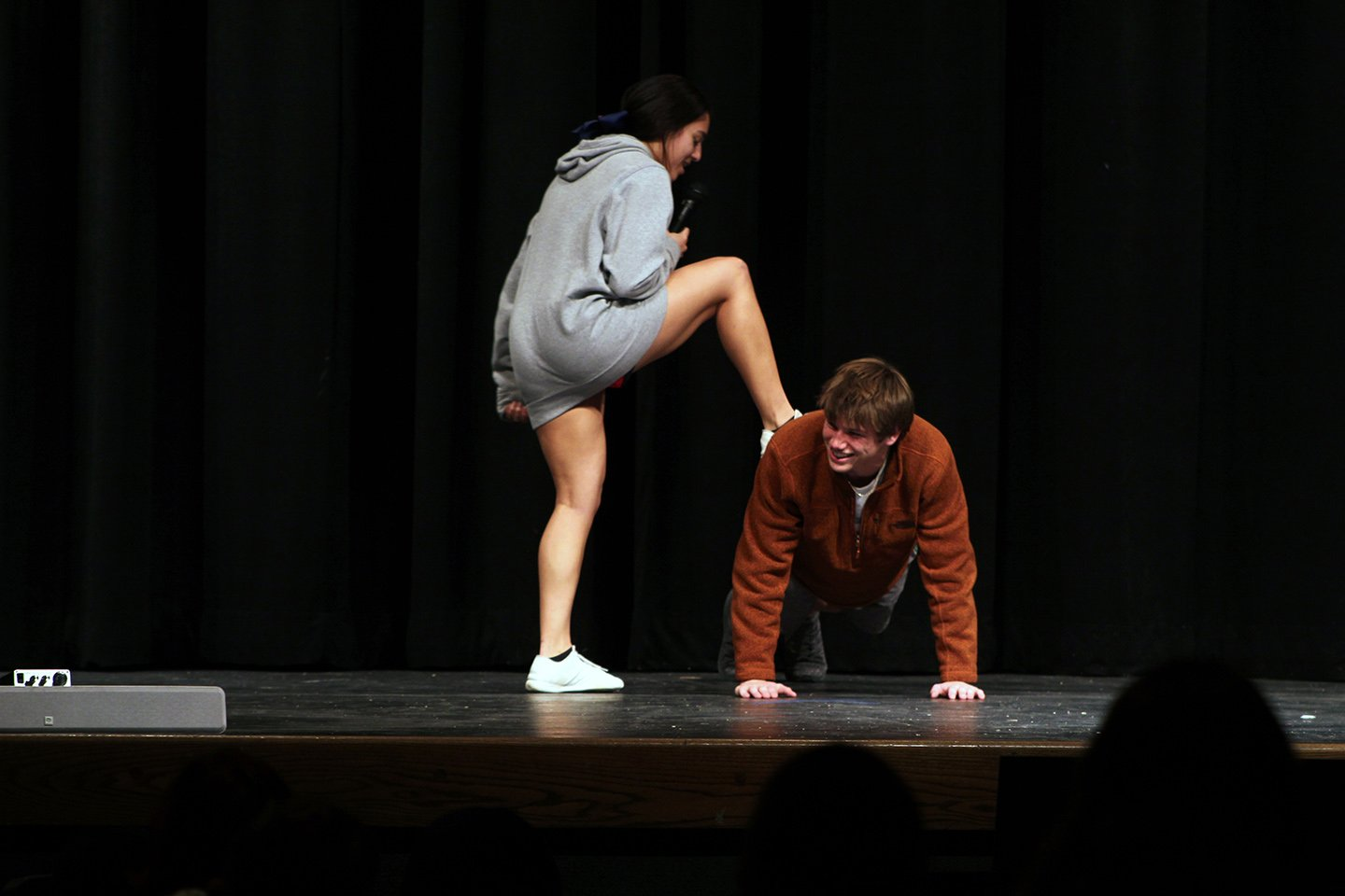 """Michael Doiel (on ground) and Mya Brown (standing) present their act """"Pushups"""" to the audience full of students with Doiel doing the pushups while Brown makes him do them."""