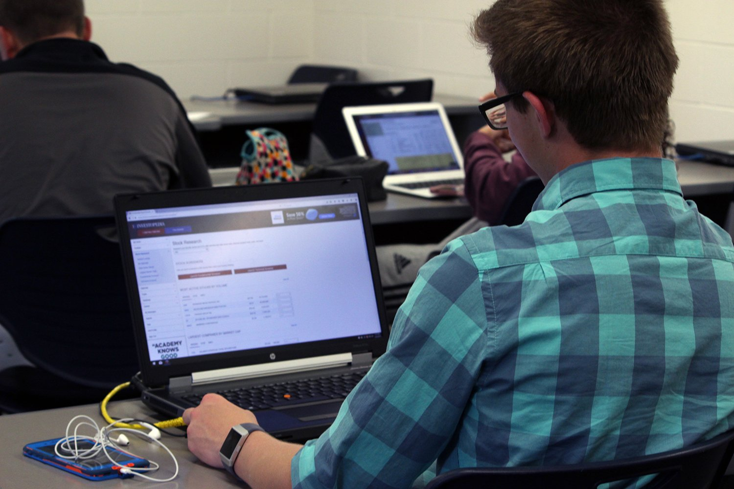 Two Timing. Junior Aaron Hoff works on his computer, looking at stocks in his Buisness and Personal Finance class. As this class ends he heads to Meadowlark where he works as the manager. Photo by Kami Bussmann