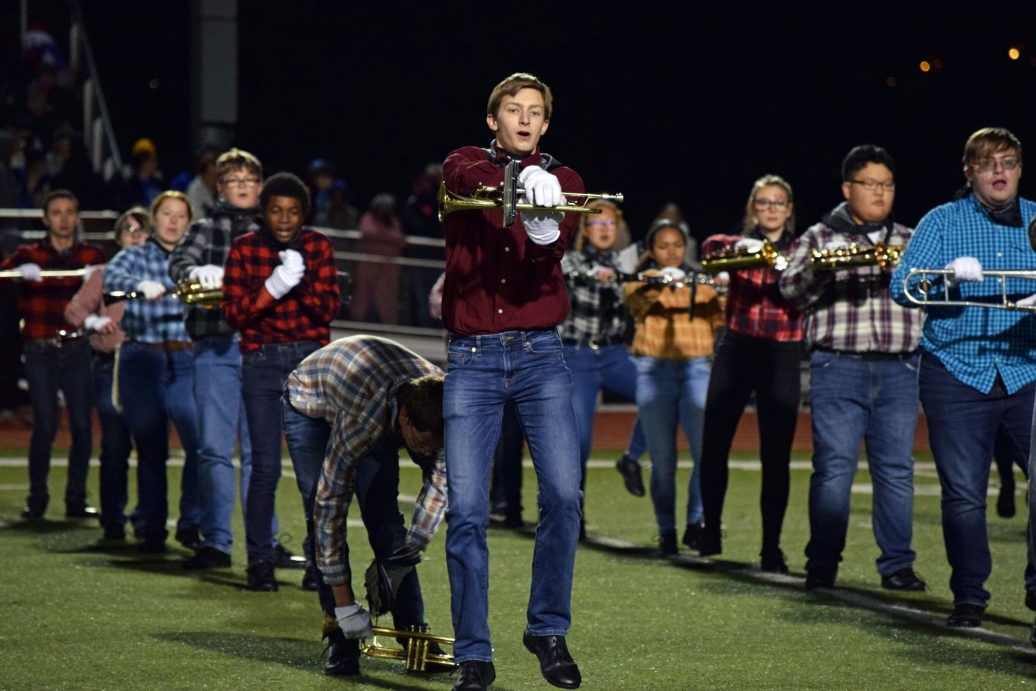 Junior ? performs with the MHS Big Blue Marching Band during their halftime show. The performance featured country music and band students dressed in classic blue jeans and flannels to sell the show. Photo by Hailey Eilert