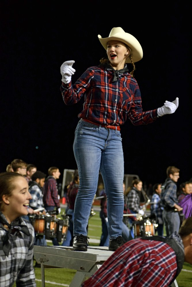 Senior Maggie Fontinini snaps to the beat as the MHS Big Blue Marching Band heads off the field at the end of their halftime performance. Fontini is a second-year drum major, other drum majors for the band this school year are seniors Jayna Schwartz and Josh Brandt. Photo by Hailey Eilert