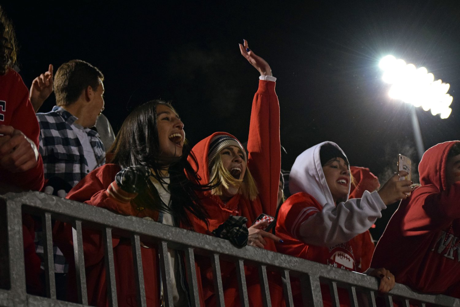Seniors Mady McCollough and Madeline Crocker cheer in voctory after the MHS Indians scored the final point of the rivalry game against Junction City. The student section stayed loud and proud during the high-stakes game. Students like Crocker and McCollough bundled up and dressed in red to stay warm and school spirited. Photo by Hailey Eielrt