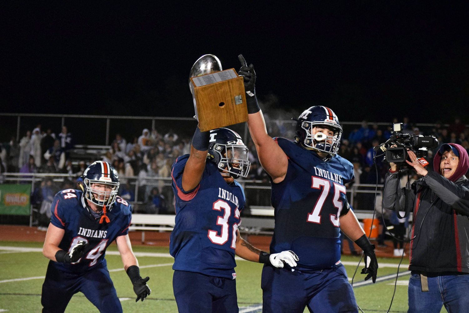 Senior BJ Young holds up the silver trophy and teammate senior Sam Shields raises his arm in victory. Manhattan High School and Junction City competed for the trophy, rivalry award and bragging rights on Oct. 11 at Bishop Stadium. The game was neck-and-neck going into the fourth quarter but MHS pulled ahead 29-28 after making the extra point in the final moments of the game. Photo by Hailey Eilert