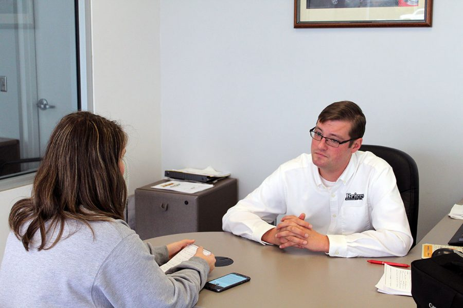 Heger, a Manhattan High junior, interviews Briggs sales representative John Windham. The interview covered the car buying process and finances.