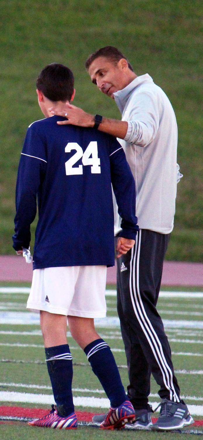 Head coach Frank Alonso walks along the field with senior Jack Easton during the Varsity boys Senior night soccer game.