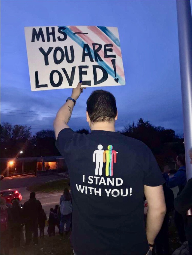 Gay+Straight+Alliance+sponsor+and+Environmental+Science+teacher+Clancey+Livingston+holds+a+sign+of+support+while+he+looks+upon+the+student+counter-protestors+--+lead+by+Student+Body+President%2C+senior+Parker+Wilson+--+as+Westboro+Baptist+Church+protests+GSA+and+the+LBGTQ%2B+community+of+Manhattan+High.+The+protests+took+place+just+outside+of+MHS+7%3A10+to+7%3A40+the+morning+of+Nov.1++