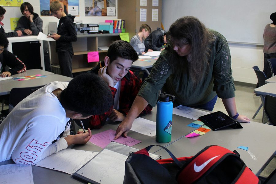 Jancy Radke points something out to Sophmores Julian Avila-Vargas and Easton Roberts during Geometry class. The class spent the period participating in an activity that combined math with the classic game Who Dunnit. It was fun and it was a good review, Roberts said.