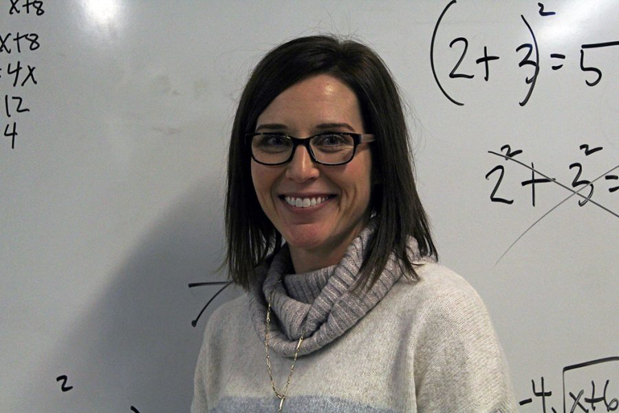Teacher Dedra Braxmeyer smiles while standing infront of the whiteboard in her classroom. Braxmeyer is a math teach at Manhattan High School who was recognized with the Teacher of the Year award.