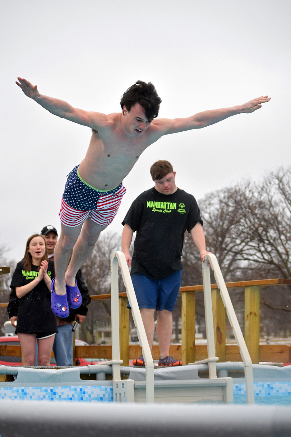 Senior Max Landsdowne belly flops into the ice-cold water during the polar plunge event on Feb. 23. Many MHS students participated in the plunge this year, the event raised money and awareness for the special olympics.
