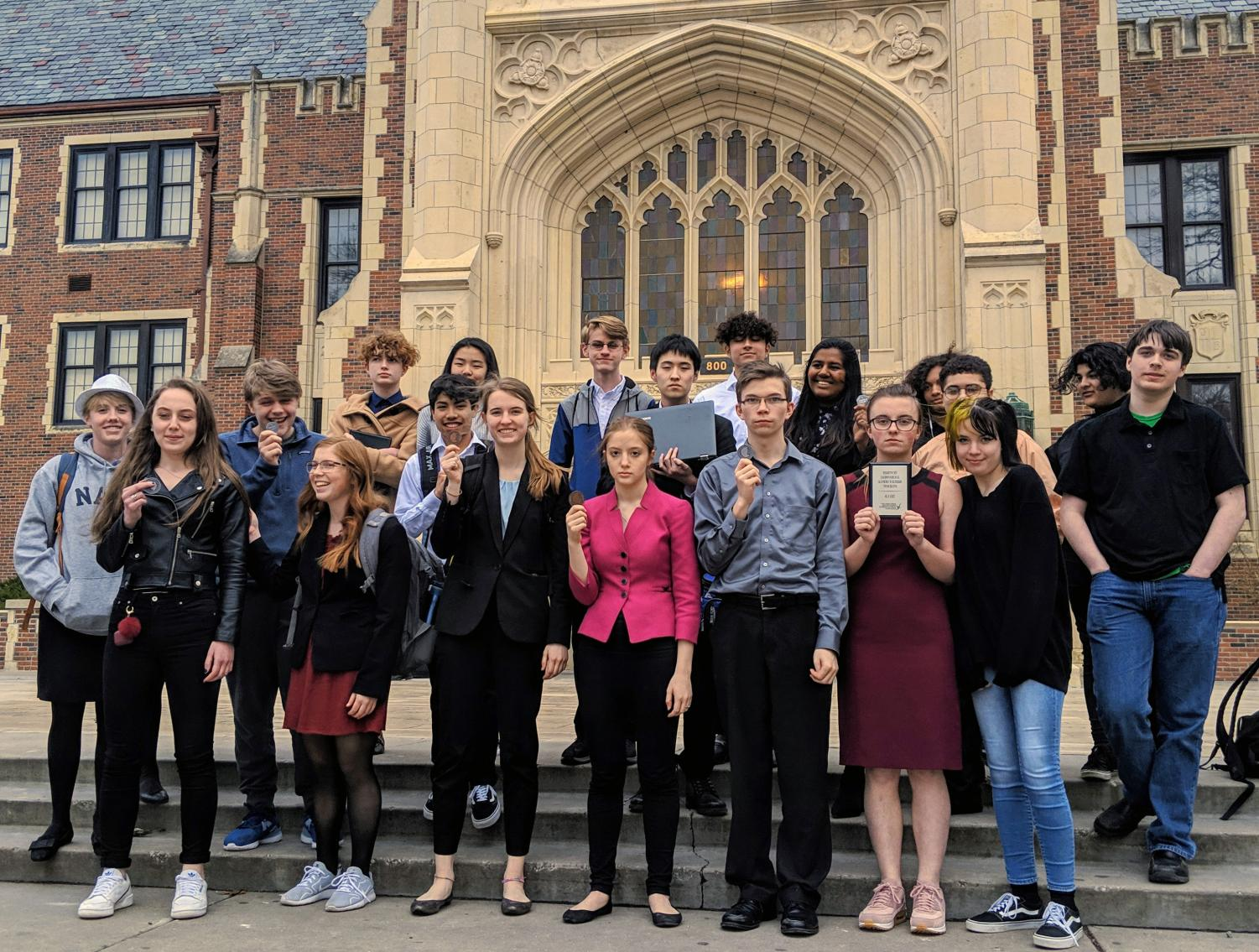 The Manhattan High Forensics team poses in front of Topeka High with their awards at their meet Saturday. The team took home another national qualification to make three total, as well as another state qualification to adorn their wall. Photo courtesy of
