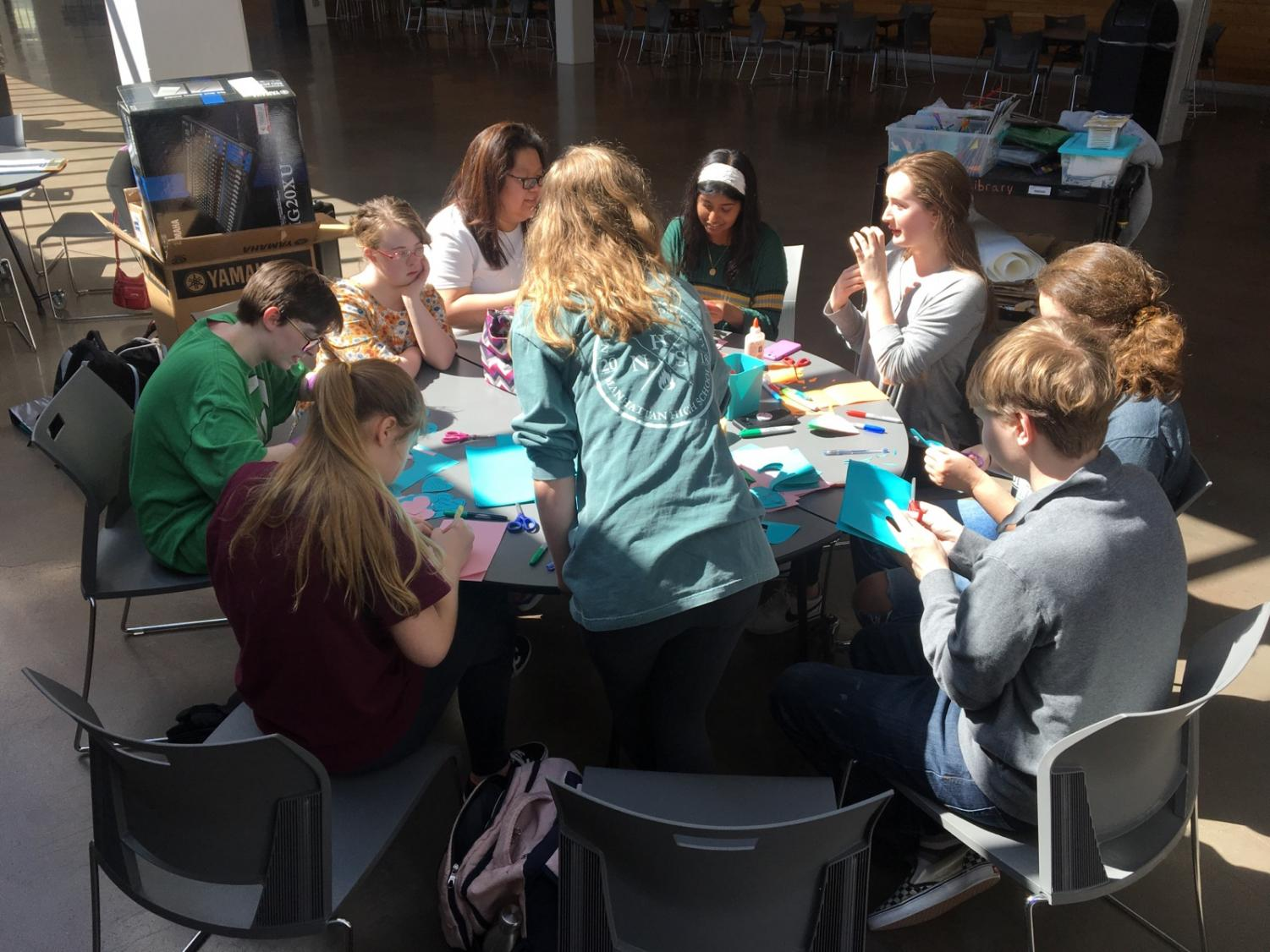 Members of the Hugs for Humanity committee paint pictures in The Commons.