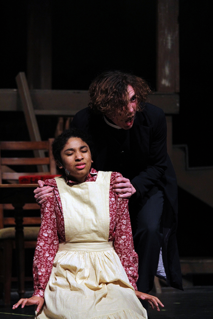 Senior Jacob Wineland, playing Reverend Hale, grips the shoulders of junior Trinity Martinez, playing Tituba, during a scene in which Wineland is urging Martinez to confess to the sin of witchcraft in