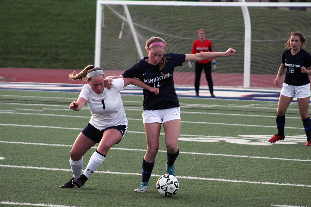 Senior Izzie Williams keeps a Hayden High School player from pushing her away from the ball Friday evening.