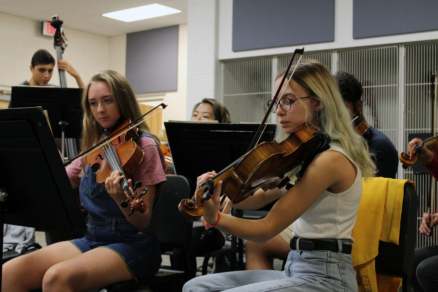 Seniors Grace Hart and Liz Efken practice their Shostakovich piece with their violas as they wait for director Nate McClendon to arrive for class. The orchestra began rehearsing earlier in the week in preparation for the day when they must play it completely by memory.