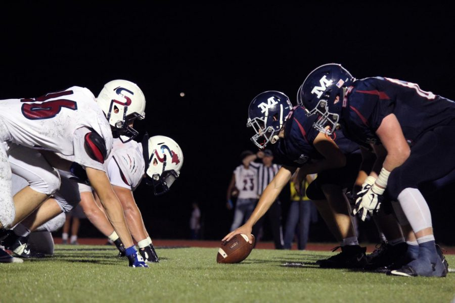The Varsity football players line up to hike the ball to the quarterback. The boys won 56-24 on Sept. 20, the annual Homecoming game.
