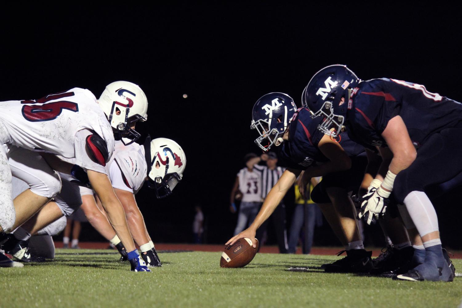 The+Varsity+football+players+line+up+to+hike+the+ball+to+the+quarterback.+The+boys+won+56-24+on+Sept.+20%2C+the+annual+Homecoming+game.+