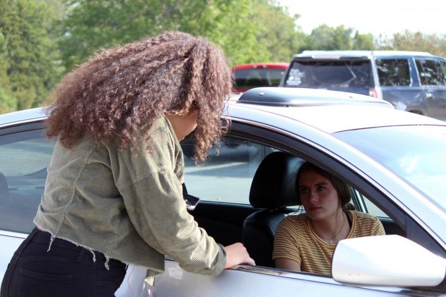 Sophomore Kaitlyn Stone talk to senior Elise Mitchell through her car window after school in the Sunset Zoo parking lot.
