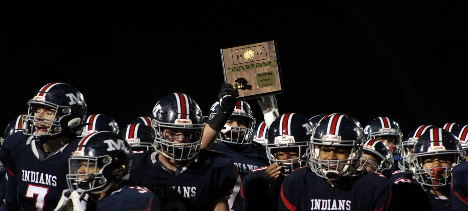The Varisty football team holds up their Regional championship plaque after winning against Lawrence Free State, 49-28. The win determined the team's next game, which is at Derby on Nov. 16.