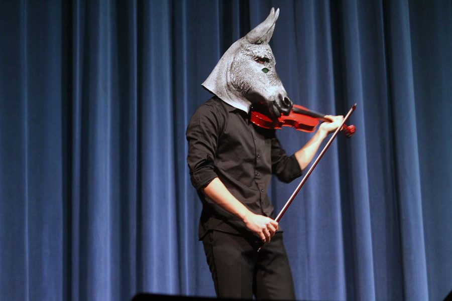 Senior Allen Zhang- as a donkey- runs onto the Rezac Auditorium stage. The Orchestravanza included many references to pop culture that involved the audience.