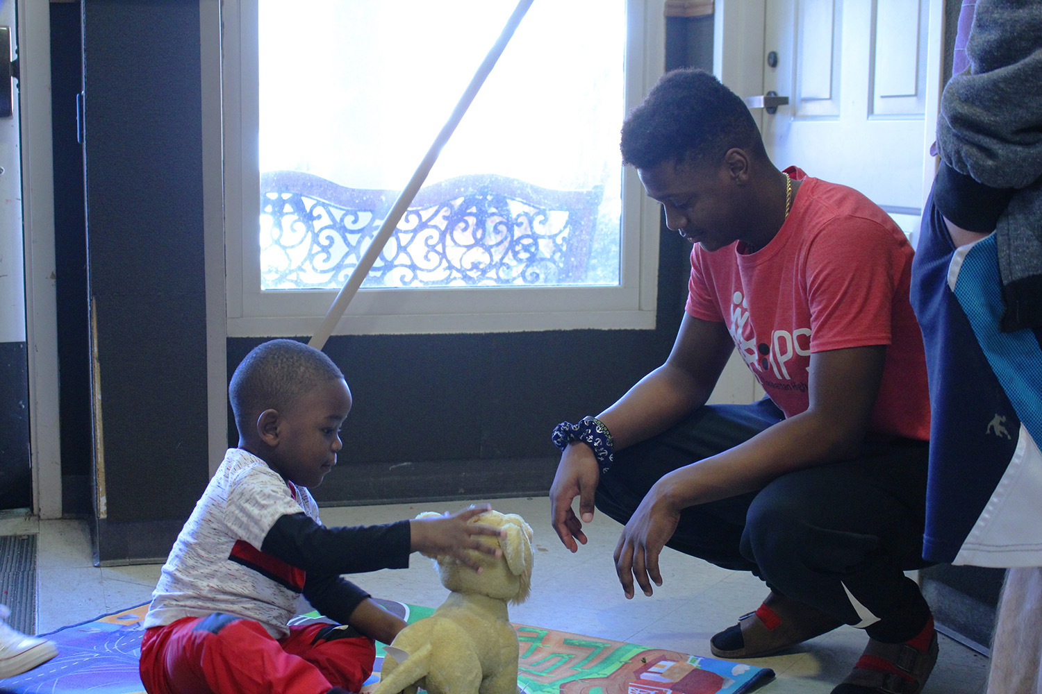 Junior Caleb DeLoach and a child from the Flint Hills Job Corps play with a stuffed toy after IPS delivered gifts to the group after Christmas.