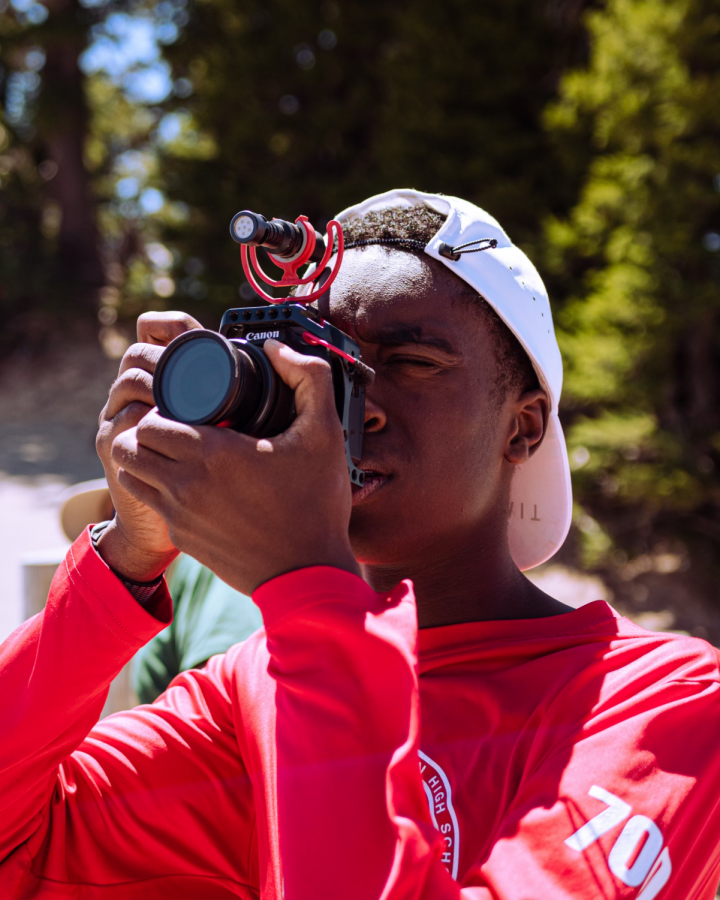 Adjusting his camera for the perfect shot, senior Max Bowyer gazes at the world through a lens. About three years ago, Bowyer started a YouTube channel and since then has participated in a number of video production opportunities to further his skills. Courtesy Photo