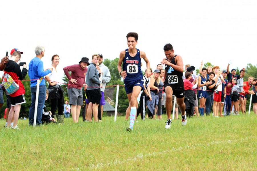 Junior+Aidan+Starling+passes+junior+Trevor+Cain+from+Washburn+Rural+just+before+crossing+the+finish+line+at+the+cross+country+Manhattan+Invitational+on+Sept.+4.+Starling+finished+in+12th+place.+Photo+by+Julianna+Poe