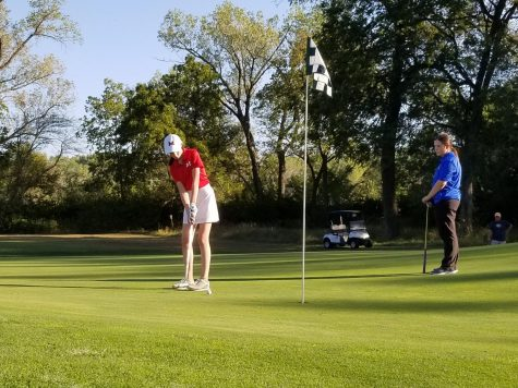 Freshman Ruby Wendt putts out on her last hole, ending with a 114 at the Manhattan Invitational on Monday. The Varsity girls golf team placed third overall as a team. Photo by Julianna Poe